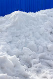 Pile snow. In front of a blue metal fence background. Free space for text Stock Photography
