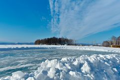 A pile of snow in front of a cleared rural roller. In the background, partly out of focus, the frozen lake Uvildy and forest winter south russia blue sky cold royalty free stock photography