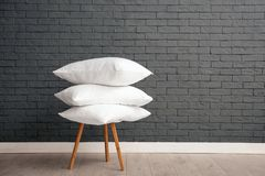 Pile of soft bed pillows on chair near brick wall. With space for text stock images
