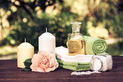 A pile of soft towels, natural essential oil and sea salt. Roses and candles. Spa set in the summer garden. Vintage tinting Stock Image
