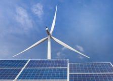 Pile solari con i generatori eolici che generano elettricità nella stazione ibrida dei sistemi della centrale elettrica sul fondo Immagini Stock