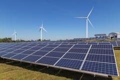 Pile solari con i generatori eolici che generano elettricità nella stazione ibrida dei sistemi della centrale elettrica sul fondo Fotografia Stock Libera da Diritti
