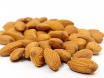 Pile of some almonds on white background. Pile of some fresh dry brown almonds on white background. useful for hair advertisement Stock Image