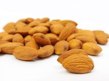 Pile of some almonds on white background. Pile of some fresh dry brown almonds on white background. useful for hair advertisement Stock Photography