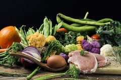 Fruit, raw vegetables, eggs and meat. A pile of some fruit and some different raw vegetables, such as cauliflower of different colors, broccolini or french beans stock photos
