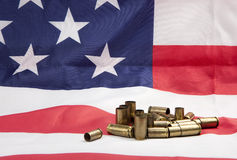 Pile of spent casings on the flag. A concept image of shell casings and an American flag Stock Image