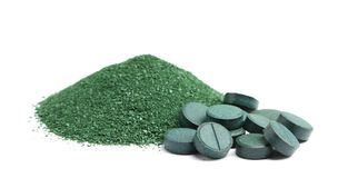 Pile of spirulina powder and tablets on background. Pile of spirulina powder and tablets on white background Stock Photos