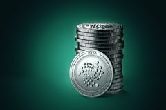 Pile or stack of silver IOTA coins on gently lit green blue background. One coin is turned towards the camera. 3D rendering new virtual money royalty free illustration