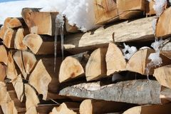 Pile of stacked firewood with snow and icicles on it. royalty free stock photos