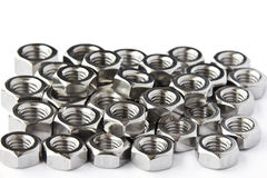 Pile of stainless steel nuts. A shop floor item, shallow DOF Stock Photos