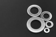 Pile Of Stainless Steel Washers. Pile of stainless steel flat washers  on a dark background Stock Images