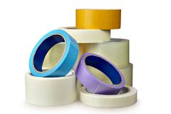 Pile of sticky tape lies on table,  white background. Transparent packing tape and colored masking tape isolated on white background, with saved clipping path Stock Photo