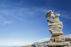 Pile of stone at the mountain. Stones pile at the mountain with the moon at blue sky Royalty Free Stock Photo