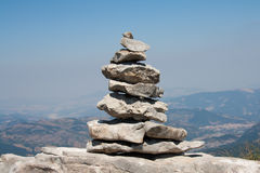 Pile of stones. Stack of stones in a mountain trail, with landscape in the background Royalty Free Stock Photography