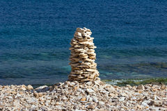 Pile of stones in balance. Stack of stones with blue sea on background Royalty Free Stock Photo
