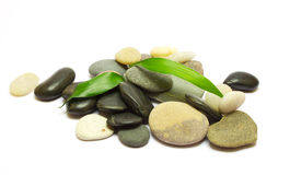 Pile of stones and bamboo leafs on white Royalty Free Stock Photos