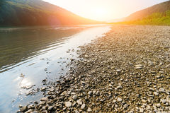 A pile of stones on the bank of the Buller River, with the river in the background and the surrounding high cliffs covered in bush. And the sun setting below a Royalty Free Stock Photo