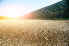 A pile of stones on the bank of the Buller River, with the river in the background and the surrounding high cliffs covered in bush. And the sun setting below a Royalty Free Stock Image