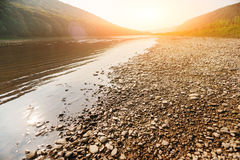A pile of stones on the bank of the Buller River, with the river in the background and the surrounding high cliffs covered in bush. And the sun setting below a Royalty Free Stock Images