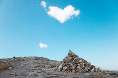 A pile of stones and cloud in the shape of heart Stock Photos