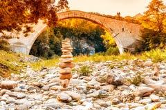 Pile of stones  and hunchback bridge Stock Photography