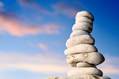 Pile of stones on seacoast. Stack of balanced pebbles, stones against colorful blue sky Stock Image