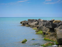 A pile of stones stretches out into the sea Royalty Free Stock Photo
