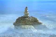 Pile of stones surrounded by blurred sea waves Stock Image