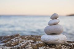 Pile of Stones on Tranquil Beach at Sunset. Tower of stones piles on top of a rock on a tranquil deserted beach at evening sunset stock photos