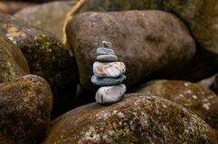 Balanced pile of stones in river. Pile of stones well balanced and placed over a mossy stone in a river royalty free stock images
