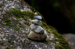 Balanced pile of stones in river. Pile of stones well balanced and placed over a mossy stone in a river stock images