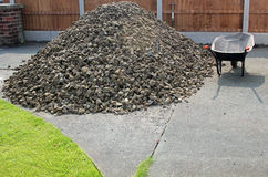 Pile of stones with wheelbarrow. On driveway Royalty Free Stock Photography