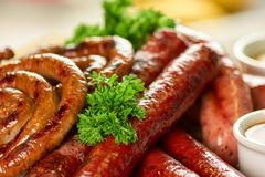 Pile of straight and coil sausages with parsley closeup. Straight and coil sausages with garnish stock image