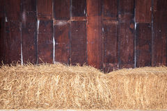 Pile of straw infront of wooden wall Stock Photos