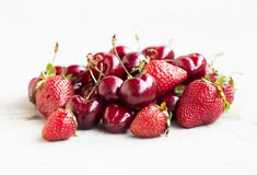 Pile of strawberries and cherries on concrete background, summer Royalty Free Stock Photos