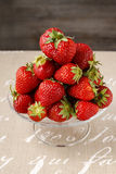Pile of strawberries on glass cake stand Stock Image