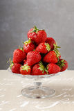 Pile of strawberries on glass cake stand Stock Images
