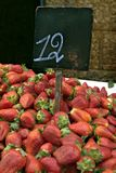 Pile of  Strawberries in the market. With a price sign with the number 12 Royalty Free Stock Photography