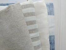 Pile of striped white grey blue linen cotton fabrics on white background. Royalty Free Stock Photos