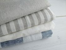 Pile of striped white grey blue linen cotton fabrics on white background. Different colours. Food photo props. Natural linen cotton fabric stock photos