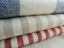 Pile of striped white grey blue red linen cotton fabrics on white background. Royalty Free Stock Photos