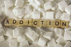 Pile of sugar cubes and addiction word in block letters as advise on calories excess and sweet unhealthy food abuse causing health. Conceptual still life with stock photos