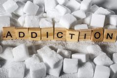 Pile of sugar cubes and addiction word in block letters as advise on calories excess and sweet unhealthy food abuse causing health. Conceptual still life with stock photo