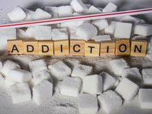 Pile of sugar cubes and addiction word in block letters as advise on calories excess and sweet unhealthy food abuse causing health. Conceptual still life with royalty free stock photography
