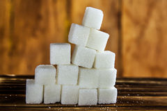 Pile of Sugar Cubes Stacking on Table over Wooden Background. Stock Photography