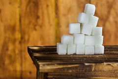 Pile of Sugar Cubes Stacking on Table over Wooden Background. Stock Photo