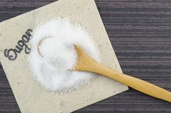 Pile of sugar and a wooden spoon full of sugar Royalty Free Stock Photography