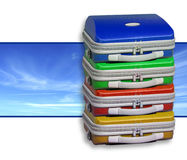 Pile of suitcases. A pile of bright suitcases against a sky panorama background. White area left for text insertion Stock Photo
