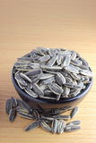 Pile of sunflower seeds in a bowl. On the wooden background Stock Photography