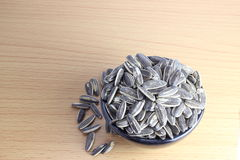 Pile of sunflower seeds in a bowl. On the wooden background Royalty Free Stock Image
